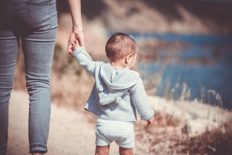 An die Hand nehmen ist schon mal eine gute Idee für Reisen mit Kindern. Foto: Unsplash/Guillaume de Germain