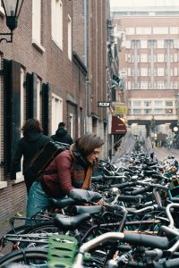 Frau an Fahrrad in Pulk von Rädern in Amsterdam. Foto: Trae Gould/Unsplash